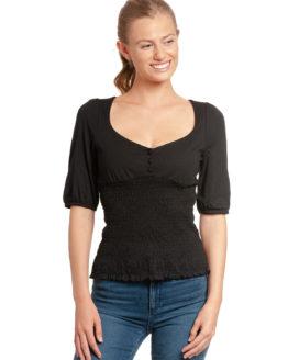 Junge Frau trägt schwarzes Top aus Modal von VIVE MARIA (FIESTA) mit halblangen Puffärmeln, kleiner Knopfleiste und gesmoktem dehnbarem Stoff. / Vorderansicht / pussyGALORE / Leipzig