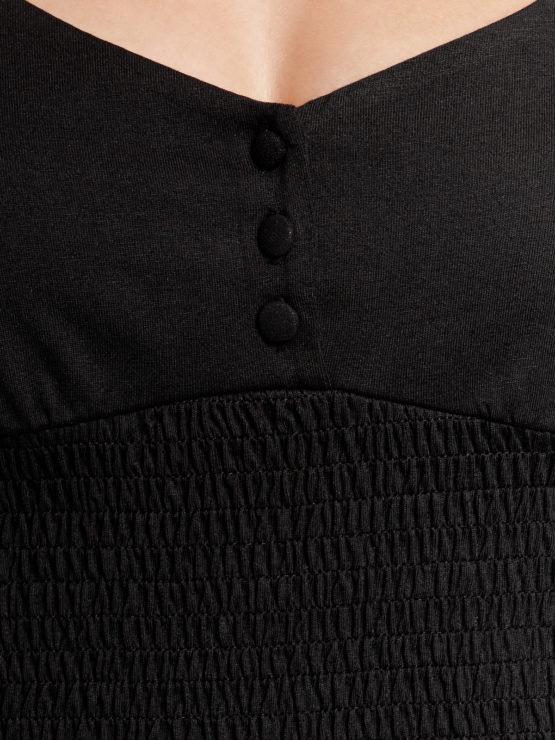 Junge Frau trägt schwarzes Top aus Modal von VIVE MARIA (FIESTA) mit halblangen Puffärmeln, kleiner Knopfleiste und gesmoktem dehnbarem Stoff. / Detailansicht 2 / pussyGALORE / Leipzig