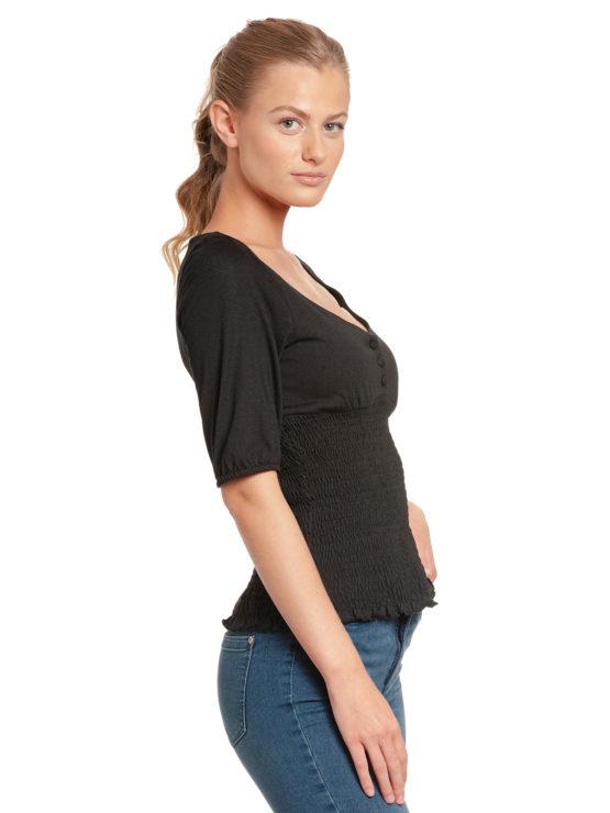 Junge Frau trägt schwarzes Top aus Modal von VIVE MARIA (FIESTA) mit halblangen Puffärmeln, kleiner Knopfleiste und gesmoktem dehnbarem Stoff. / Seitenansicht / pussyGALORE / Leipzig