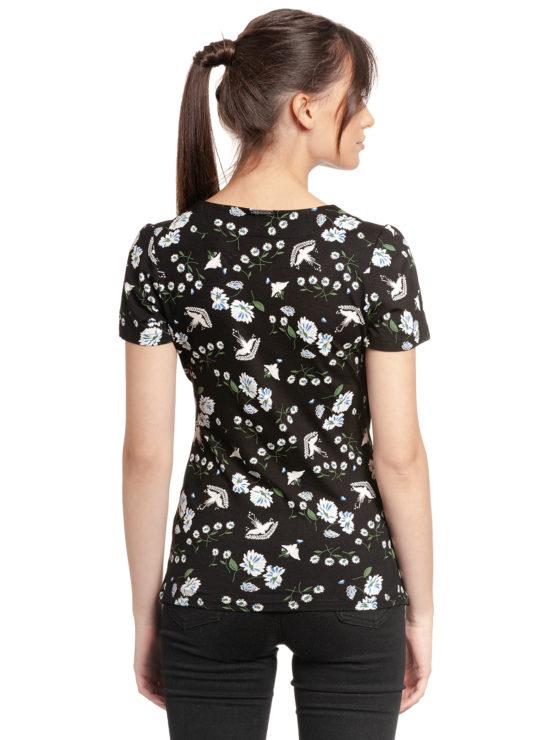 Junge Frau trägt schwarzes figurbetontes Shirt aus Viskose mit floralem Muster von VIVE MARIA (PARADISE SUMMER) in Wickeloptik mit Bordüre aus transparenter Spitze. / Rückenansicht / pussyGALORE / Leipzig