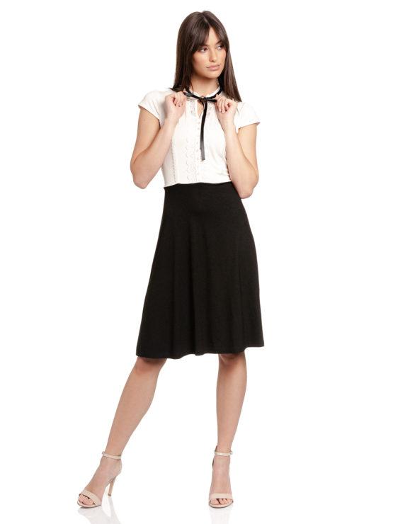 Junge Frau trägt schwarz-weißes Kleid von VIVE MARIA (PARIS AFTERNOON) mit einer Schleife aus Samt am Kragen. / Vorderansicht / pussyGALORE / Leipzig