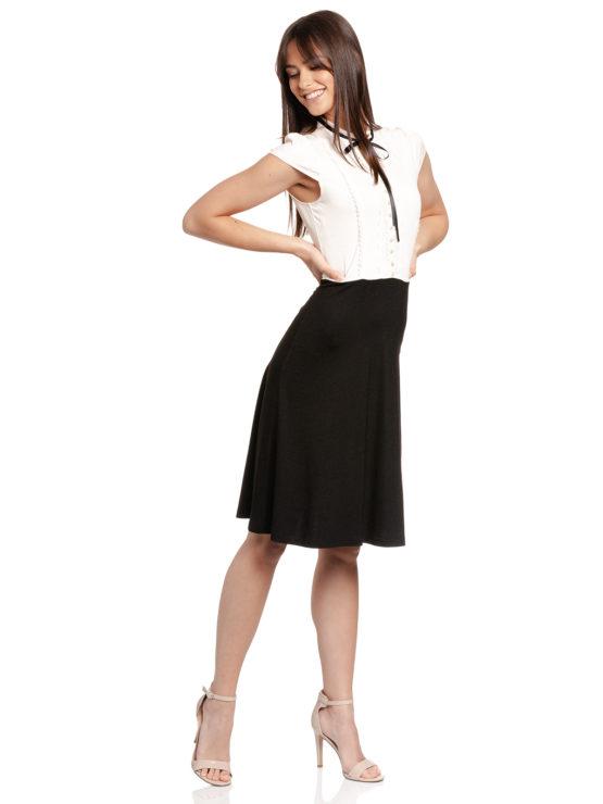 Junge Frau trägt schwarz-weißes Kleid von VIVE MARIA (PARIS AFTERNOON) mit einer Schleife aus Samt am Kragen./ Seitenansicht / pussyGALORE / Leipzig