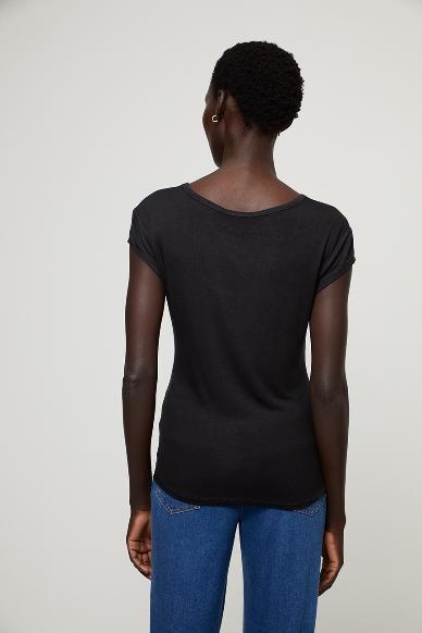 Junge Frau trägt ausgeschnittenes Rundhals-Shirt von SURKANA (BLAM) aus Viskose mit kurzen angesetzten Ärmeln. / Schwarz / Rückenansicht / pussyGALORE / Leipzig