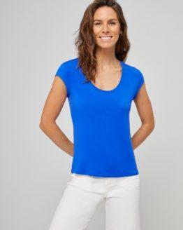 Junge Frau trägt ausgeschnittenes Rundhals-Shirt von SURKANA (BLAM) aus Viskose mit kurzen angesetzten Ärmeln. / Blau, Schwarz / pussyGALORE / Leipzig