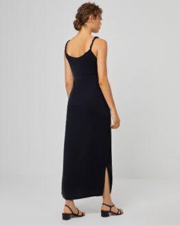 Junge Frau trägt langes schwarzes Kleid von SURKANA (BEKK) aus Modal mit seitlichem Beinschlitz und in sich gedrehten Trägern. / Rückenansicht / pussyGALORE / Leipzig