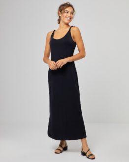 Junge Frau trägt langes schwarzes Kleid von SURKANA (BEKK) aus Modal mit seitlichem Beinschlitz und in sich gedrehten Trägern. / pussyGALORE / Leipzig