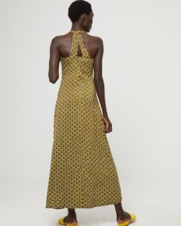 Junge Frau trägt langes Kleid von aus Viskose in Art Deco Muster von SURKANA (HOVI) mit Neckholder-Ausschnitt und verkreuztem Trägerdetail am Rücken. / Rückenansicht / pussyGALORE / Leipzig