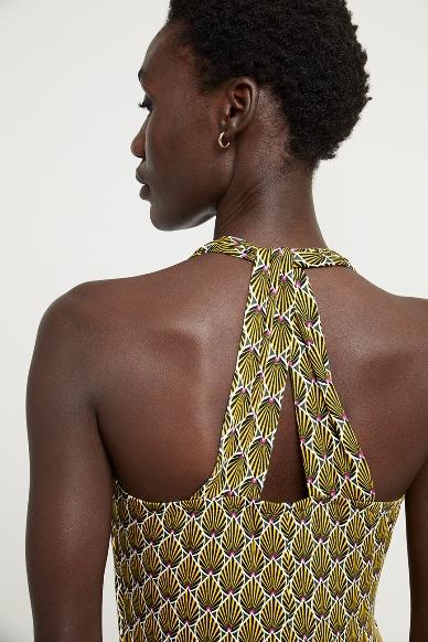 Junge Frau trägt langes Kleid von aus Viskose in Art Deco Muster von SURKANA (HOVI) mit Neckholder-Ausschnitt und verkreuztem Trägerdetail am Rücken. / Detailansicht / pussyGALORE / Leipzig