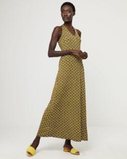 Junge Frau trägt langes Kleid von aus Viskose in Art Deco Muster von SURKANA (HOVI) mit Neckholder-Ausschnitt und verkreuztem Trägerdetail am Rücken. / pussyGALORE / Leipzig