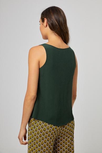 Junge Frau trägt ärmellose Bluse aus Viskose von SURKANA (LIVI) mit Knopfleiste und V-Ausschnitt. / Kaki / Rückenansicht / pussyGALORE / Leipzig