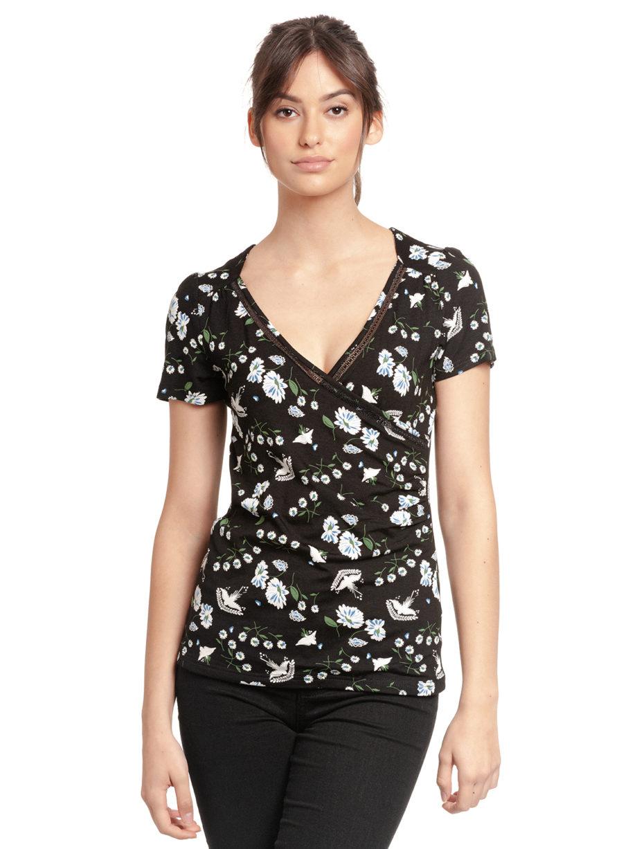 Junge Frau trägt schwarzes figurbetontes Shirt aus Viskose mit floralem Muster von VIVE MARIA (PARADISE SUMMER) in Wickeloptik mit Bordüre aus transparenter Spitze. / Vorderansicht / pussyGALORE / Leipzig