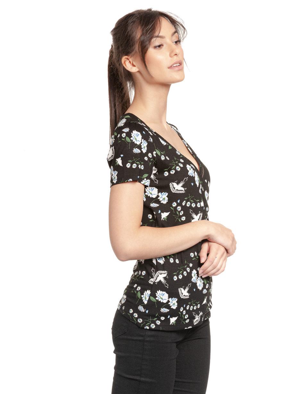 Junge Frau trägt schwarzes figurbetontes Shirt aus Viskose mit floralem Muster von VIVE MARIA (PARADISE SUMMER) in Wickeloptik mit Bordüre aus transparenter Spitze. / Seitenansicht / pussyGALORE / Leipzig