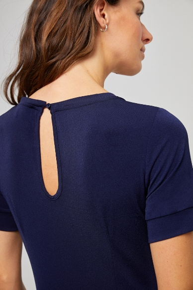 Junge Frau trägt kurzärmeligen Jumpsuit von SURKANA (LINI) in Midi-Länge mit V-Ausschnitt und Taschen. / Navy / Detailansicht 2 / pussyGALORE / Leipzig