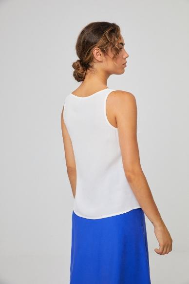 Junge Frau trägt ärmellose Bluse aus Viskose von SURKANA (LIVI) mit Knopfleiste und V-Ausschnitt. / Weiß / Rückenansicht / pussyGALORE / Leipzig