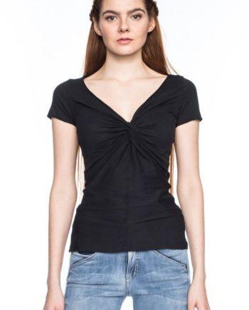 Frau trägt schwarzes figurnahes Shirt von ATO BERLIN (ANGIE) aus Biobaumwolle mit kurzen Ärmeln, offenen Saumkanten mit Kettelnaht und geknoteten V-Ausschnitt. GOTS zertifiziert, hergestellt in Portugal. / pussyGALORE / Leipzig