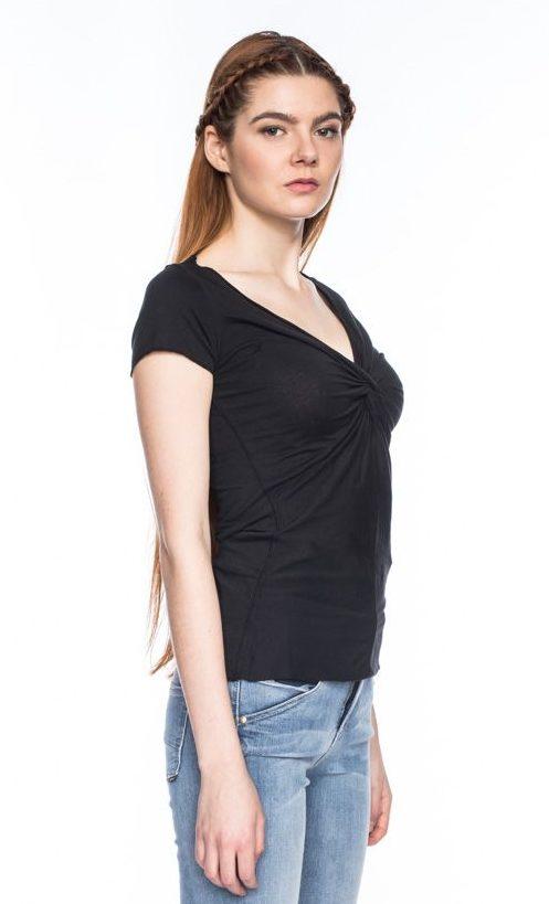 Frau trägt schwarzes figurnahes Shirt von ATO BERLIN (ANGIE) aus Biobaumwolle mit kurzen Ärmeln, offenen Saumkanten mit Kettelnaht und geknoteten V-Ausschnitt. GOTS zertifiziert, hergestellt in Portugal. / Seitenansicht / pussyGALORE / Leipzig