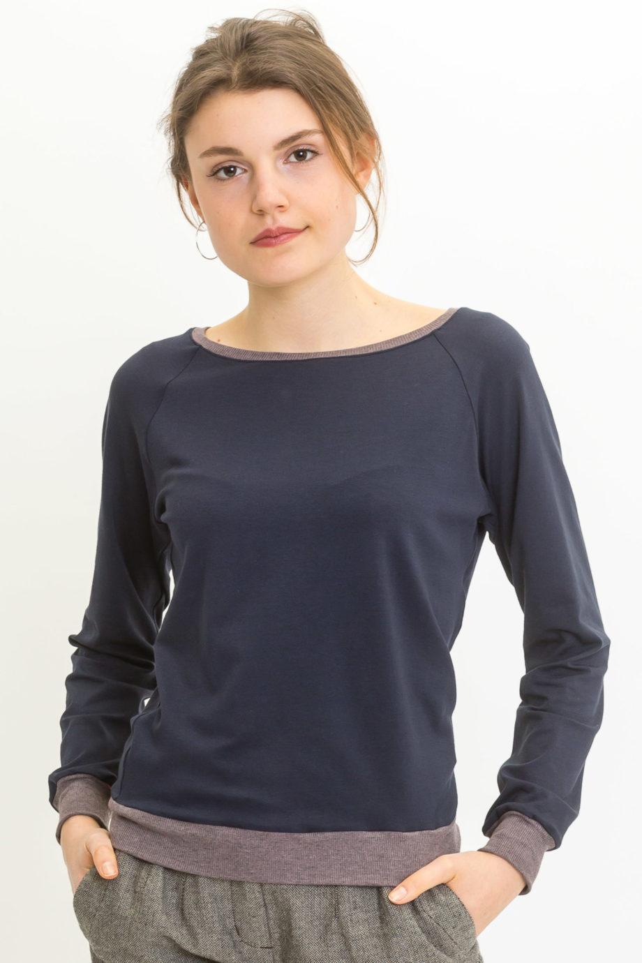 Frau trägt marineblaues Langarmshirt von UVR CONNECTED (LORAINA) aus Viskose mit U-Boot-Ausschnitt, Raglanärmeln und Kontrastbündchen. Fair produziert in Europa. / pussyGALORE / Leipzig