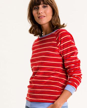 Frau trägt gestreiftes Sweatshirt von UVR CONNECTED (LORAINA) aus rotem Nicki-Stoff mit U-Boot-Ausschnitt und hellblauen Bündchen an Hüfte und Ärmeln. Fair produziert in Europa. / pussyGALORE / Leipzig