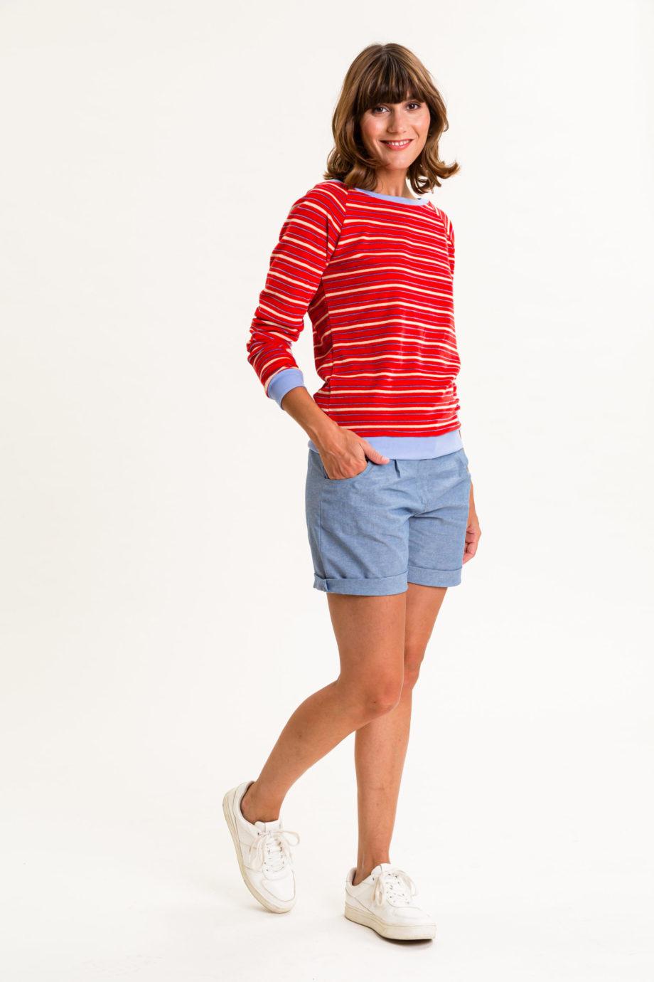 Frau trägt gestreiftes Sweatshirt von UVR CONNECTED (LORAINA) aus rotem Nicki-Stoff mit U-Boot-Ausschnitt und hellblauen Bündchen an Hüfte und Ärmeln. Fair produziert in Europa. / Vorderansicht 2/ pussyGALORE / Leipzig