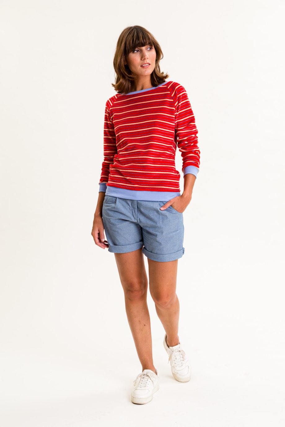 Frau trägt gestreiftes Sweatshirt von UVR CONNECTED (LORAINA) aus rotem Nicki-Stoff mit U-Boot-Ausschnitt und hellblauen Bündchen an Hüfte und Ärmeln. Fair produziert in Europa. / Vorderansicht / pussyGALORE / Leipzig