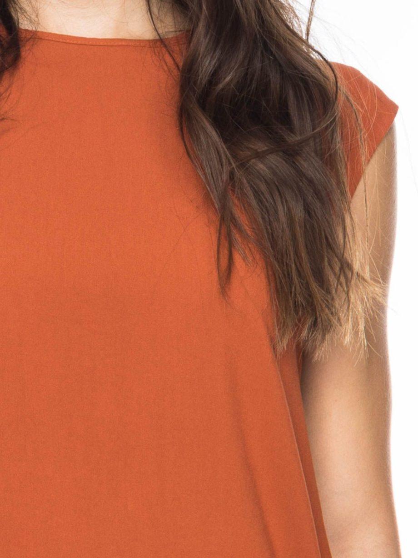 Frau trägt Top von ATO BERLIN (FEMKE) in Orange aus recycelter Viskose vorn und Lyocell mit Elastananteil hinten. Mit Rundhals-Ausschnitt, angeschnittenen Ärmeln und Keyhole-Verschluss im Nacken. GOTS zertifiziert, hergestellt in Portugal. / Detailansicht / Picant / pussyGALORE / Leipzig