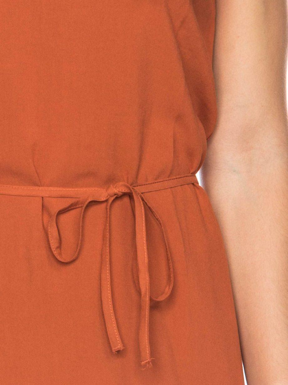 Frau trägt kurzes orangenes Kleid von ATO BERLIN (GORETTI) aus recycelter Viskose vorn und Lyocell mit Elastananteil hinten. Mit Kordel in der Taille, Rundhals-Ausschnitt, angeschnittenen Ärmeln und Keyhole-Verschluss. GOTS zertifiziert, hergestellt in Portugal. / Detailansicht / pussyGALORE / Leipzig
