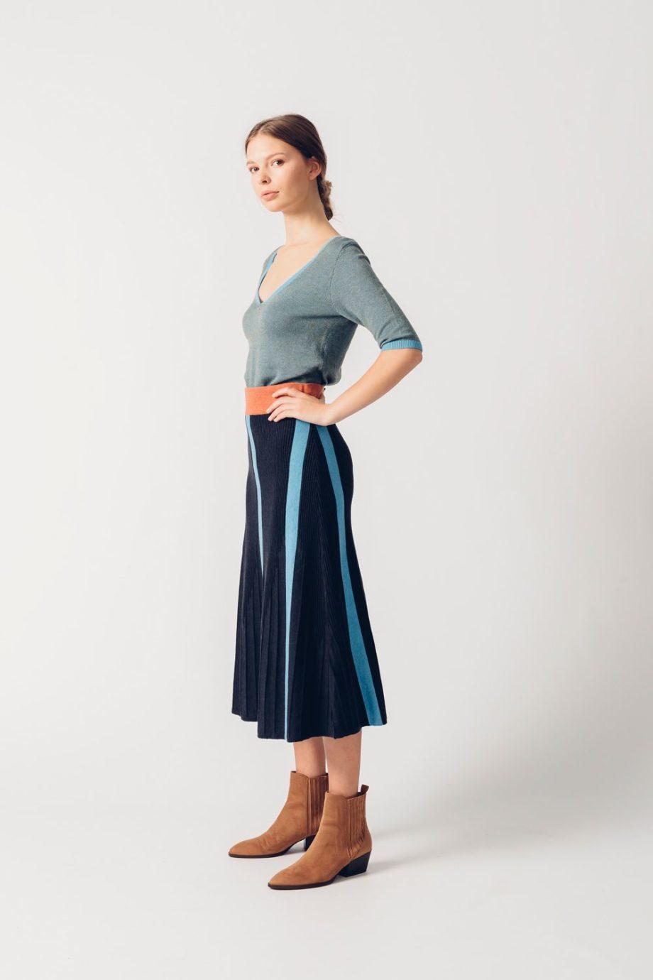 Frau trägt dunkelblauen Strickrock von SKFK (HEKATE) in Midi-Länge aus Biobaumwolle mit hellblauen Längsstreifen und braunem Gummizug. / Seitenansicht / pussyGALORE / Leipzig