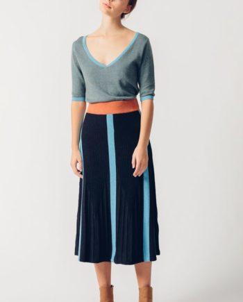Frau trägt dunkelblauen Strickrock von SKFK (HEKATE) in Midi-Länge aus Biobaumwolle mit hellblauen Längsstreifen und braunem Gummizug. / pussyGALORE / Leipzig