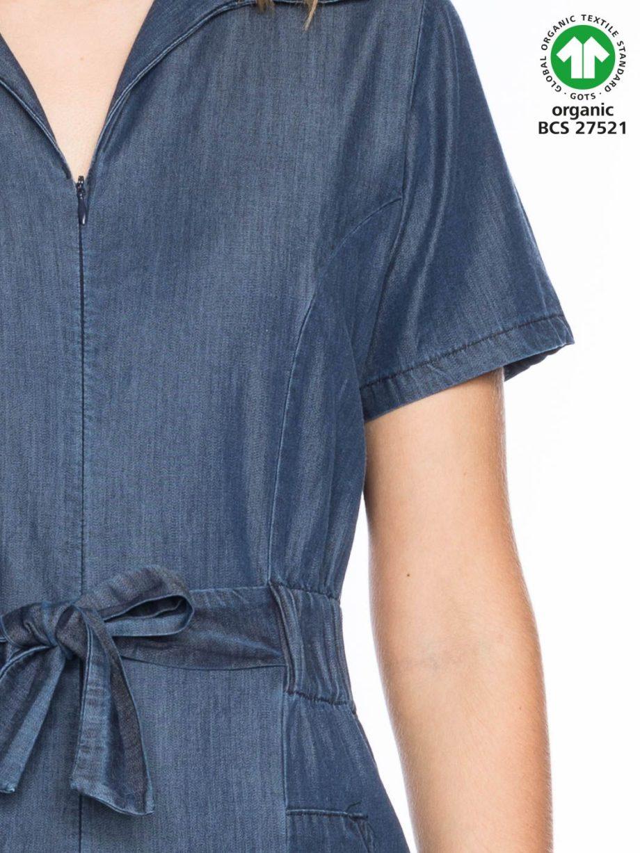Frau trägt Jumpsuit von ATO BERLIN (OLIVIA) aus leichter Biobaumwolle in Denim-Otik mit kurzen Ärmeln, V-Ausschnitt, elastischem Gummiband und seitlichen Eingriffstaschen. Schliesst vorne mit einem Reissverschuss und Gürtelband. GOTS zertifiziert, hergestellt in Portugal. / Detailansicht / pussyGALORE / Leipzig