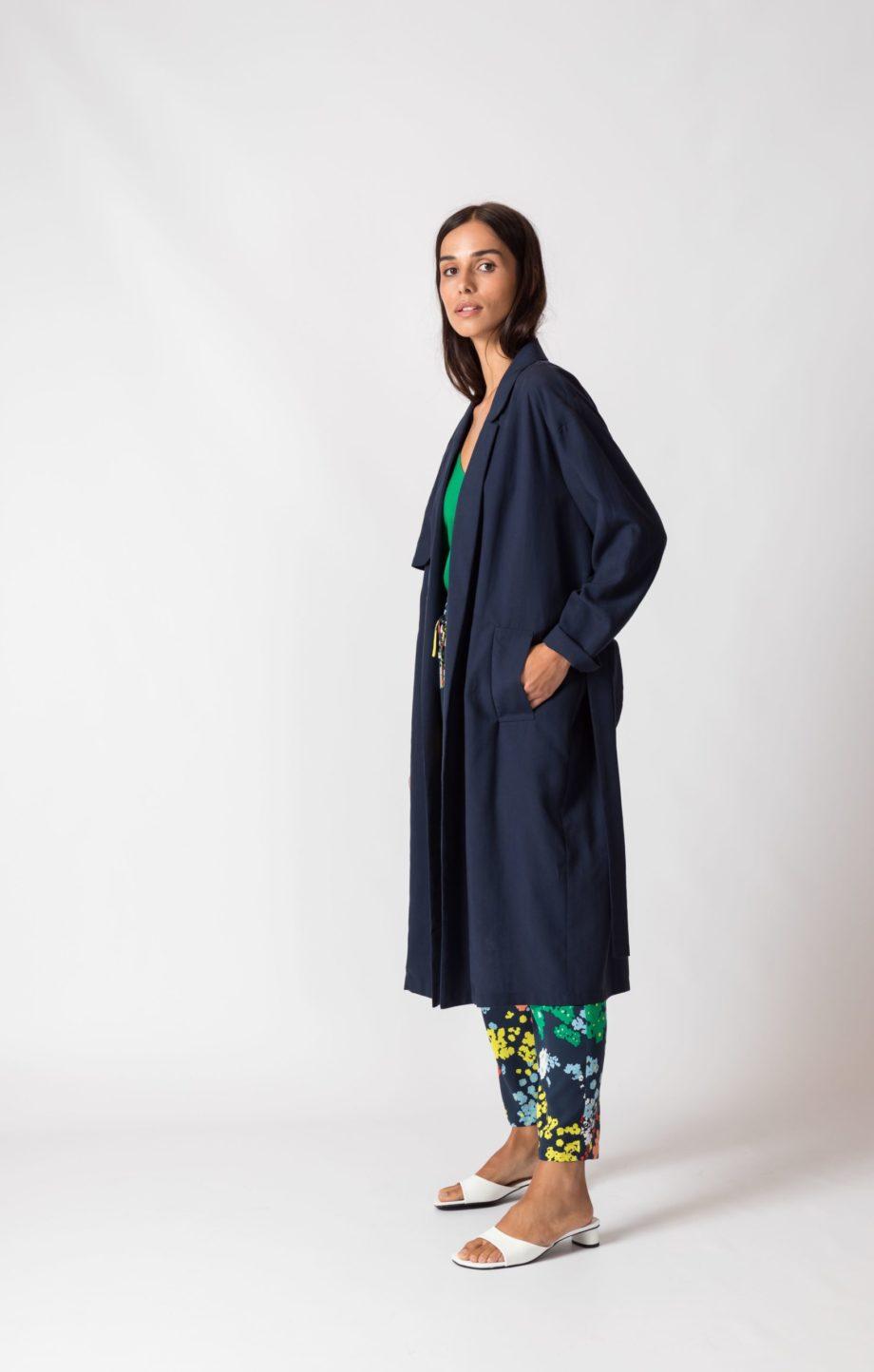 Frau trägt dunkelblauen Trenchcoat von SKFK (LIDE) mit abnehmbarem Gürtelband und seitlichen Eingriffstaschen in Midi-Länge. Fließende Kontur durch weiches Lycocell. Nachhaltig. / Seitenansicht / pussyGALORE / Leipzig