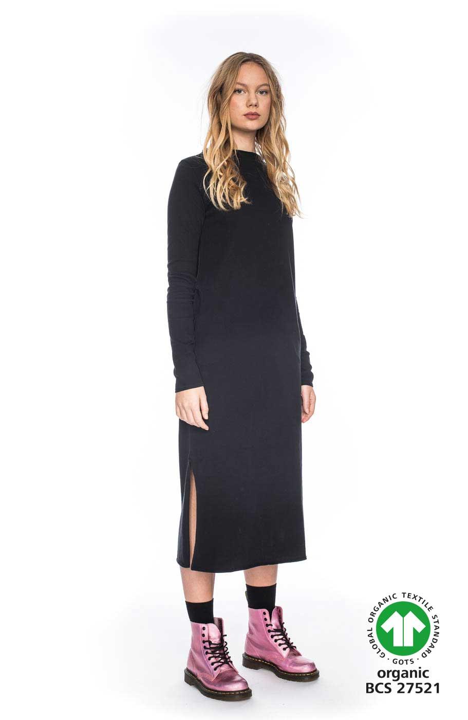 Frau trägt samtig schwarzes Kleid von ATO BERLIN (MAAIKE) in Midi-Länge aus Biobaumwolle mit hohem Rundhals-Ausschnitt und seitlichen Eingriffstaschen. Bewegungsfreiheit durch geraden Schnitt und seitliche Schlitze. GOTS zertifiziert, hergestellt in Portugal. / Seitenansicht / pussyGALORE / Leipzig