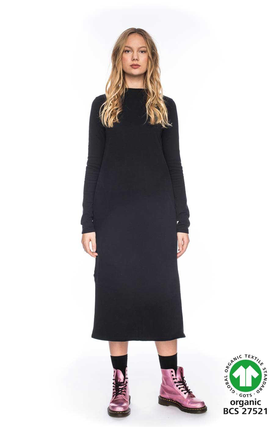 Frau trägt samtig schwarzes Kleid von ATO BERLIN (MAAIKE) in Midi-Länge aus Biobaumwolle mit hohem Rundhals-Ausschnitt und seitlichen Eingriffstaschen. Bewegungsfreiheit durch geraden Schnitt und seitliche Schlitze. GOTS zertifiziert, hergestellt in Portugal. / pussyGALORE / Leipzig