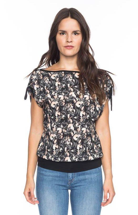 Frau trägt kurzärmliges Shirt von ATO BERLIN (MONA) aus recycelter Viskose mit floralem Print in Weiß und Apricot auf schwarzem Grund. Legere Passform mit Hüftbund und U-Boot-Ausschnitt mit Bindebändern in den Schulternähten. GOTS zertifiziert, hergestellt in Portugal. / pussyGALORE / Leipzig