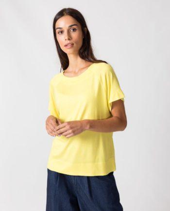 Frau trägt Basic Shirt von SKFK (NAHIERA) aus recycelter Viskose in Zitronengelb mit kurzen Raglanärmeln, Rundhals-Ausschnitt und abgerundetem Saum. / pussyGALORE / Leipzig