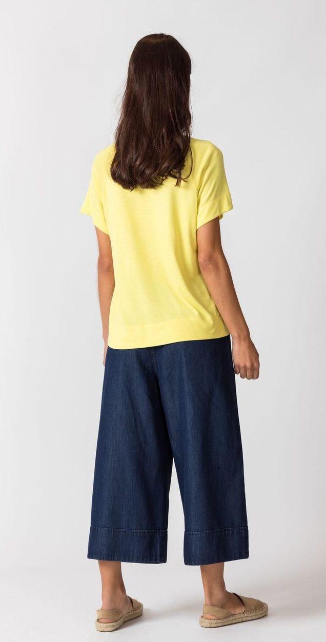 Frau trägt Basic Shirt von SKFK (NAHIERA) aus recycelter Viskose in Zitronengelb mit kurzen Raglanärmeln, Rundhals-Ausschnitt und abgerundetem Saum. / Rückenansicht / pussyGALORE / Leipzig