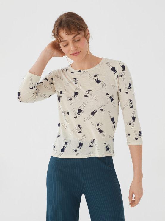 Frau trägt Shirt von NICE THINGS (FOAM PRINTED) mit Rundhals-Ausschnitt in Dreiviertel-Armlänge aus Baumwoll-Mischgewebe in Ecru mit dunkelblauem Print aus Schwimmerinnen. / Bauhaus / Vorderansicht / pussyGALORE / Leipzig
