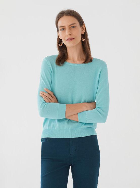 Frau trägt leichten Pullover von NICE THINGS (BASIC ROUND NECK) aus Baumwoll-Nylon-Mischung mit Rundhals-Ausschnitt, gerippten Borten und seitlichen Schlitzen am Bund in Dreiviertel-Armlänge. / Light Blue / Vorderansicht / pussyGALORE / Leipzig