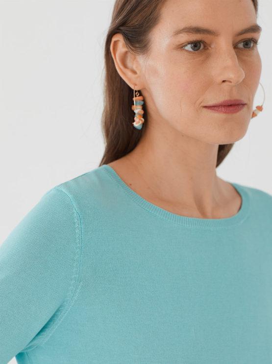 Frau trägt leichten Pullover von NICE THINGS (BASIC ROUND NECK) aus Baumwoll-Nylon-Mischung mit Rundhals-Ausschnitt, gerippten Borten und seitlichen Schlitzen am Bund in Dreiviertel-Armlänge. / Light Blue / Detailansicht / pussyGALORE / Leipzig