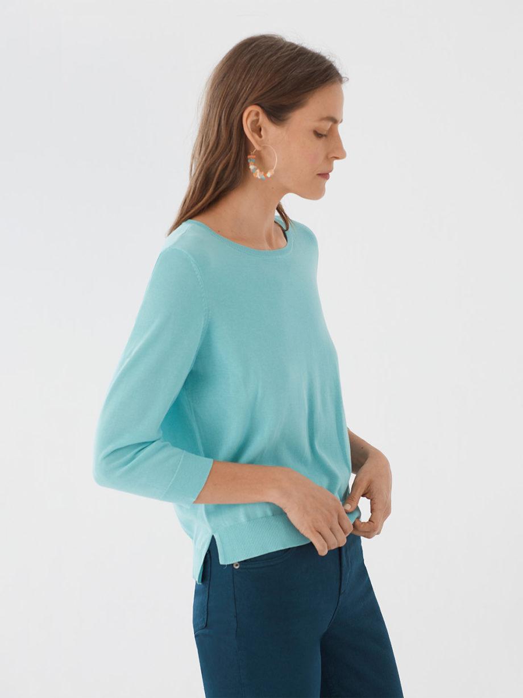 Frau trägt leichten Pullover von NICE THINGS (BASIC ROUND NECK) aus Baumwoll-Nylon-Mischung mit Rundhals-Ausschnitt, gerippten Borten und seitlichen Schlitzen am Bund in Dreiviertel-Armlänge. / Light Blue / Seitenansicht / pussyGALORE / Leipzig