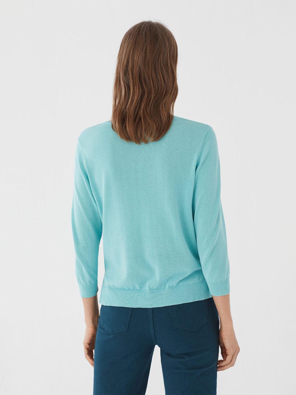Frau trägt leichten Pullover von NICE THINGS (BASIC ROUND NECK) aus Baumwoll-Nylon-Mischung mit Rundhals-Ausschnitt, gerippten Borten und seitlichen Schlitzen am Bund in Dreiviertel-Armlänge. / Light Blue / Rückenansicht / pussyGALORE / Leipzig