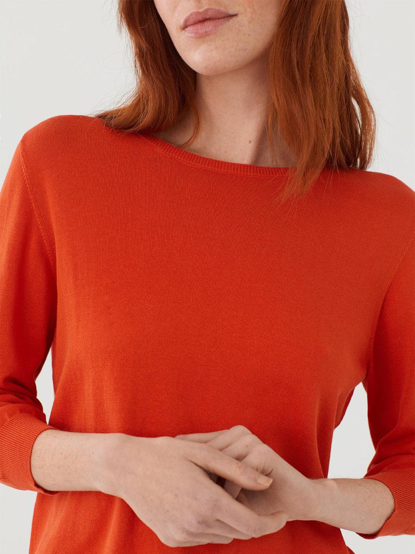 Frau trägt leichten Pullover von NICE THINGS (BASIC ROUND NECK) aus Baumwoll-Nylon-Mischung mit Rundhals-Ausschnitt, gerippten Borten und seitlichen Schlitzen am Bund in Dreiviertel-Armlänge. / Intense Or / Detailansicht / pussyGALORE / Leipzig