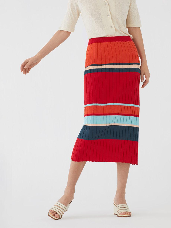 Frau trägt schmalgeschnittenen Midirock von NICE THINGS (RIB STRIPED) in rot-blau gestreiftem Rippstrick aus Baumwolle mit elastischem Bund. / Bauhaus / Vorderansicht 1 / pussyGALORE / Leipzig
