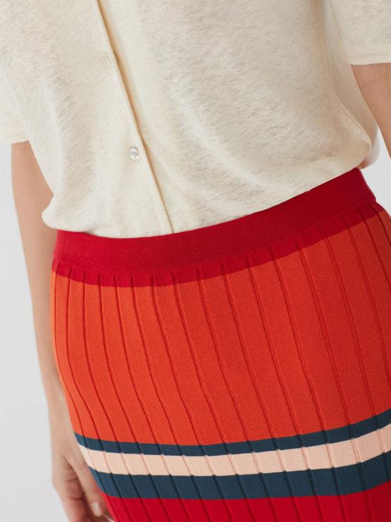 Frau trägt schmalgeschnittenen Midirock von NICE THINGS (RIB STRIPED) in rot-blau gestreiftem Rippstrick aus Baumwolle mit elastischem Bund. / Bauhaus / Detailansicht / pussyGALORE / Leipzig