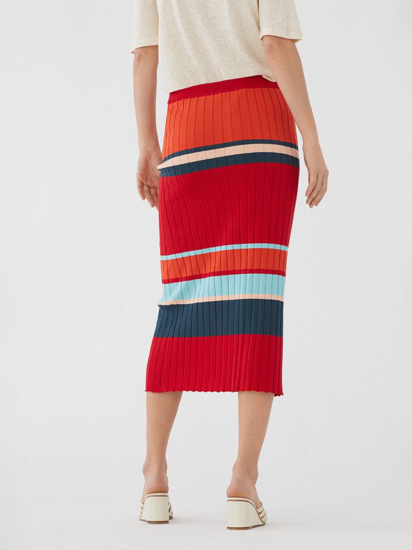 Frau trägt schmalgeschnittenen Midirock von NICE THINGS (RIB STRIPED) in rot-blau gestreiftem Rippstrick aus Baumwolle mit elastischem Bund. / Bauhaus / Rückenansicht / pussyGALORE / Leipzig
