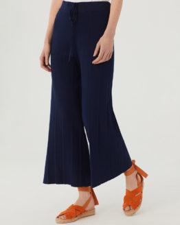 Frau trägt blaue plissierte Culotte von NICE THINGS (PLEATED WIDE) aus Strickviskose mit weitem Bein, elastischem Bund und Bindegürtel. / Adieu Tristesse / Vorderansicht / pussyGALORE / Leipzig