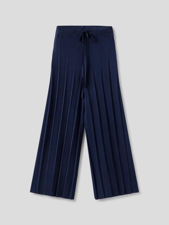 Frau trägt blaue plissierte Culotte von NICE THINGS (PLEATED WIDE) aus Strickviskose mit weitem Bein, elastischem Bund und Bindegürtel. / Adieu Tristesse / pussyGALORE / Leipzig