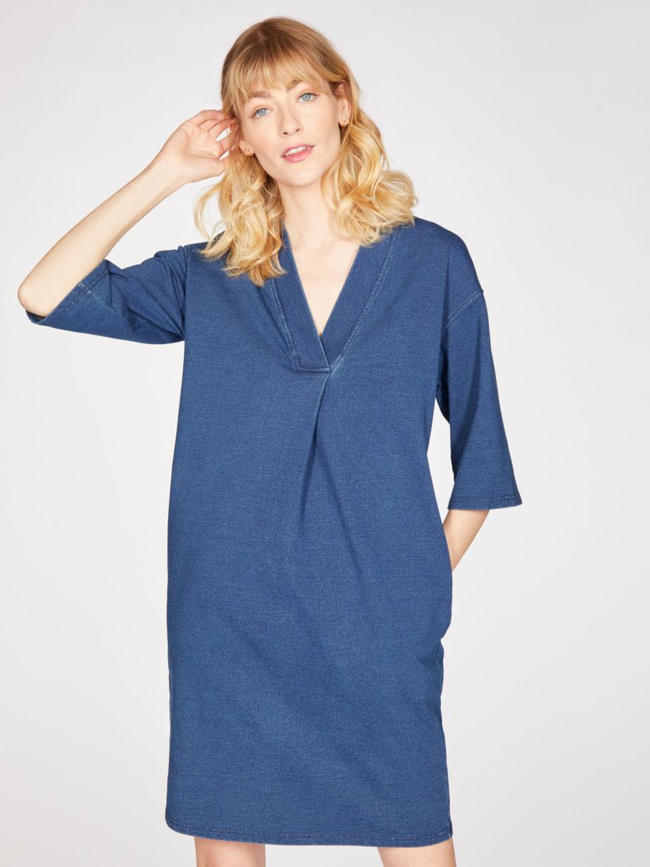 Frau trägt Kleid in Kokon-Passform von THOUGHT (SKYLAR LOOPBACK) aus Biobaumwolle in Denim-Optik mit V-Ausschnitt, versteckten Tasche und dreiviertellangen Kimonoärmeln. Loopback-Stoff mit natürlichem Indigo gefärbt. / pussyGALORE / Leipzig