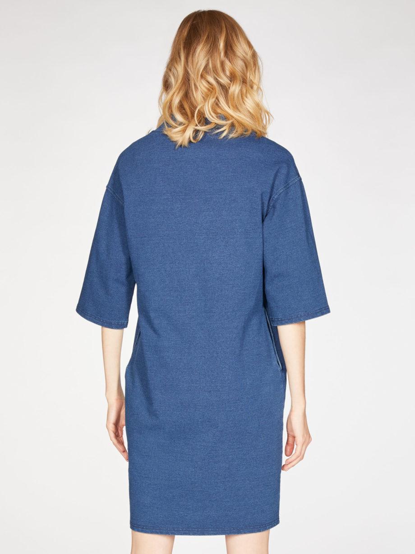 Frau trägt Kleid in Kokon-Passform von THOUGHT (SKYLAR LOOPBACK) aus Biobaumwolle in Denim-Optik mit V-Ausschnitt, versteckten Tasche und dreiviertellangen Kimonoärmeln. Loopback-Stoff mit natürlichem Indigo gefärbt. / Rückenansicht / pussyGALORE / Leipzig