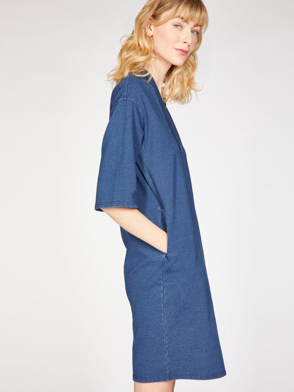 Frau trägt Kleid in Kokon-Passform von THOUGHT (SKYLAR LOOPBACK) aus Biobaumwolle in Denim-Optik mit V-Ausschnitt, versteckten Tasche und dreiviertellangen Kimonoärmeln. Loopback-Stoff mit natürlichem Indigo gefärbt. / Seitenansicht 2 / pussyGALORE / Leipzig