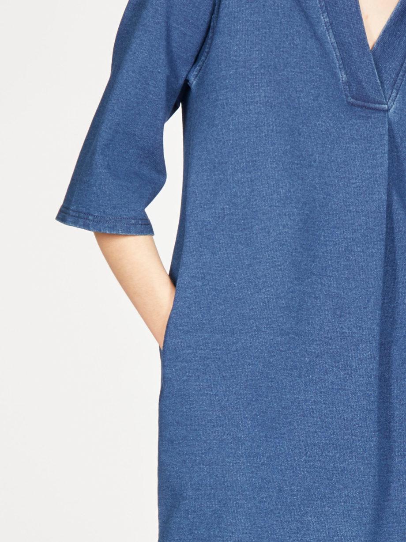 Frau trägt Kleid in Kokon-Passform von THOUGHT (SKYLAR LOOPBACK) aus Biobaumwolle in Denim-Optik mit V-Ausschnitt, versteckten Tasche und dreiviertellangen Kimonoärmeln. Loopback-Stoff mit natürlichem Indigo gefärbt. / Detailansicht / pussyGALORE / Leipzig